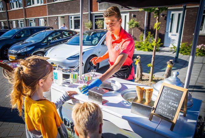 Daniël verkoopt ijsjes vanuit zijn ijskar in een straat in Puttershoek.