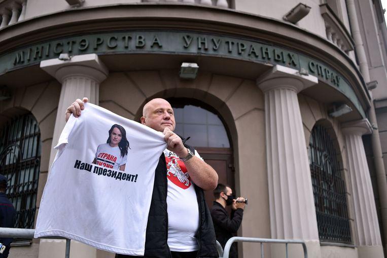 Een man houdt voor het ministerie van Binnenlandse Zaken een T-shirt omhoog met een foto van Svetlana Tichanovskaja en de tekst: 'Onze president'. Beeld AFP