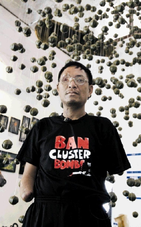 Slachtoffer van een clusterbom bij een kunstwerk gemaakt uit bomonderdelen in Vientiane in Laos. (FOTO AFP) Beeld