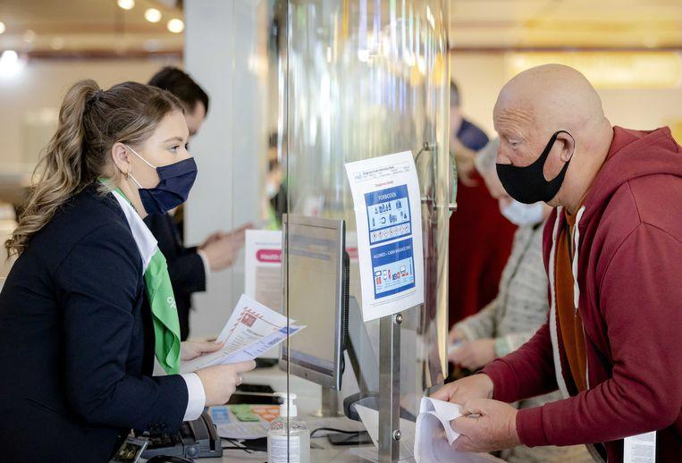Reizigers overhandigen hun negatieve pcr-test bij de incheckbalie. Beeld ANP