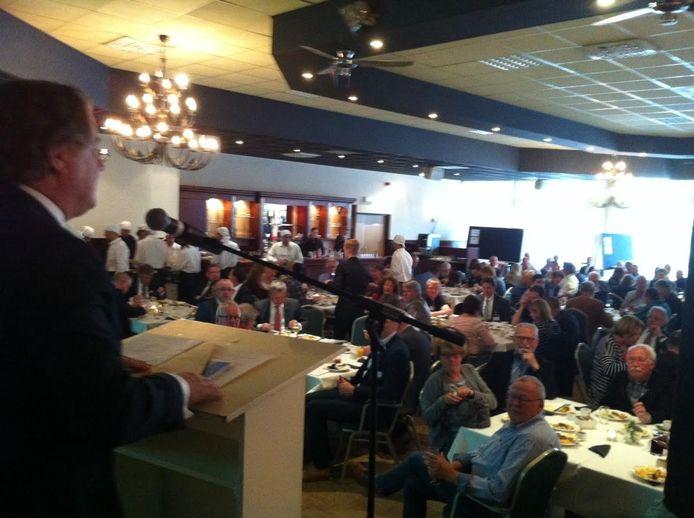 Commissaris van de koning Wim van de Donk spreekt een volle zaal raadsleden toe in Boeke