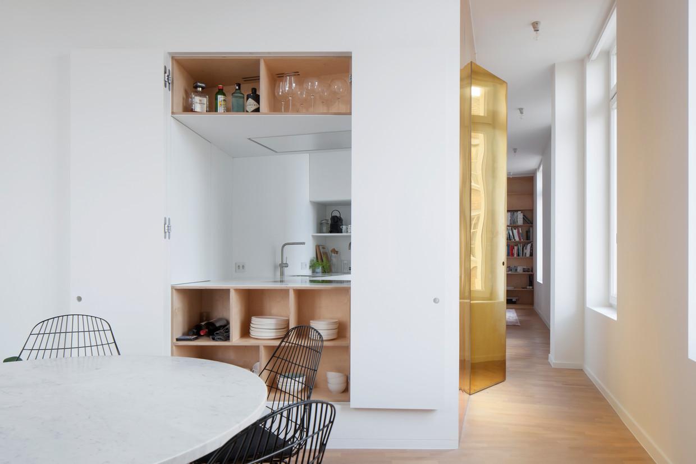 Het keukenblok zit verstopt in een compact volume dat rechtstreeks in verbinding staat met de eetkamer. Alle toestellen kunnen handig weggestoken worden achter een schuifpaneel.  Beeld Johnny Umans