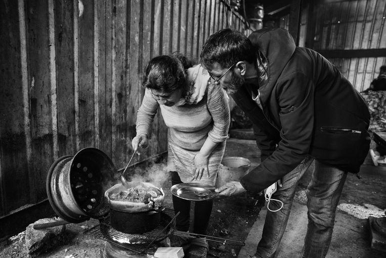 Een ouder echtpaar uit Afghanistan viert de avondmaaltijd in de hangar waarin ze wonen. Beeld Eddy van wessel