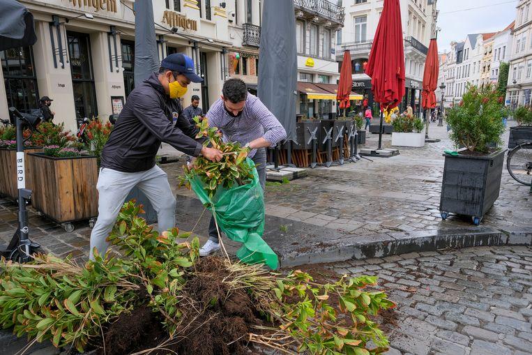 Café-uitbaters maken hun terras op de Brusselse Grote Markt klaar voor zaterdag. Beeld Marc Baert