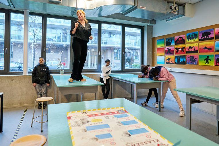 Dramadocent Judith Sluijter probeert leerlingen af te leiden die zich moeten concentreren in de les 'Superkrachten in je hoofd'. Beeld Phil Nijhuis