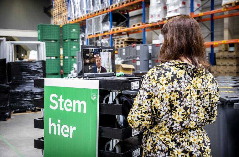Koning Willem-Alexander (op computerbeeldscherm) tijdens een digitaal bezoek aan een depot waar in aanloop naar de Tweede Kamerverkiezingen allerlei verkiezingsmateriaal ligt opgeslagen van de gemeente Rotterdam. Beeld ANP