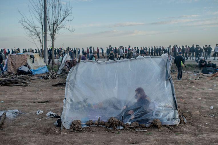 Een Syrische vrouw zit met haar zoon in een tent terwijl anderen wachten op voedseldistributie voor de grensovergang van Turkije naar Griekenland, in Edirne. Beeld AFP