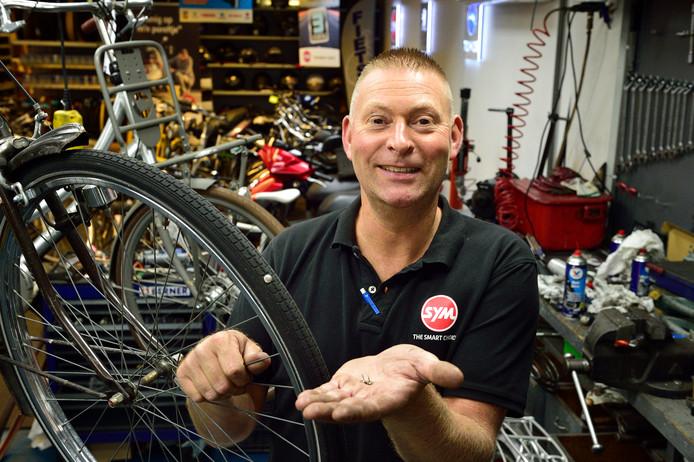 Fietsenmaker Louwerenburg. Eigenaar Peter van den Heuvel met een door punaises geteisterde fiets.