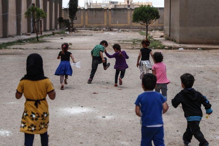 Kinderen spelen op de speelplaats van een school in Ghouta, die gebruikt wordt voor ontheemden.  Beeld EPA