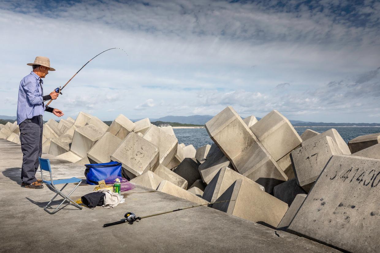 Een visser staat in Okuma, waar de Fukushima-kerncentrale staat, bij de zeemuur die is gebouwd ter bescherming tegen een volgende tsunami. Beeld Getty Images