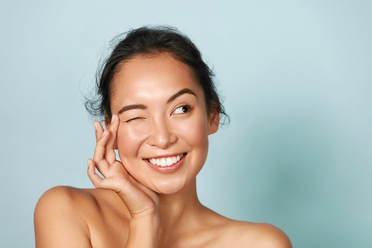 Skin care. Woman with beauty face touching healthy facial skin portrait. Beautiful smiling asian girl model with natural makeup touching glowing hydrated skin on blue background closeup Beeld Getty Images/iStockphoto