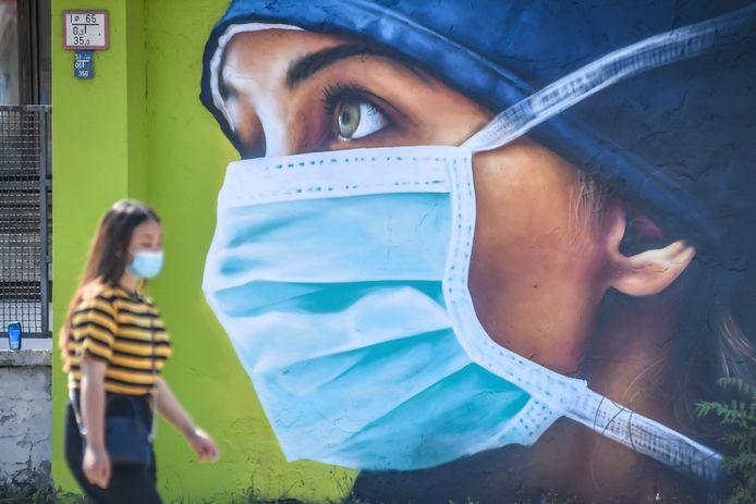 Een vrouw met mondmasker loopt voorbij een muurschildering van een vrouw met mondmasker in Milaan. Het percentage mondkapdragers in Italië is één van de hoogste van de wereld.