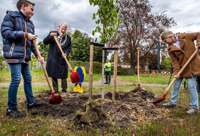 Burgemeester Hans Gaillard, Luuk van den Akker en Juka de Bruin planten een Anne Frankboom in park Vroonhoven.