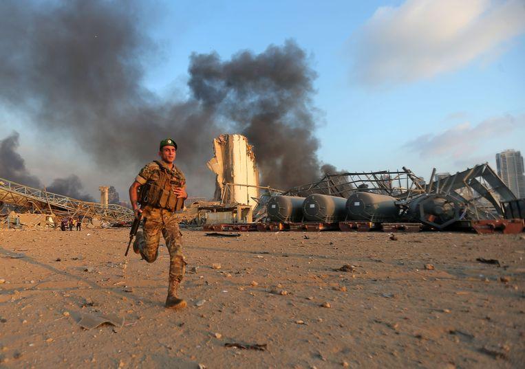 Een soldaat rent richting de plaats van de explosie.   Beeld AFP