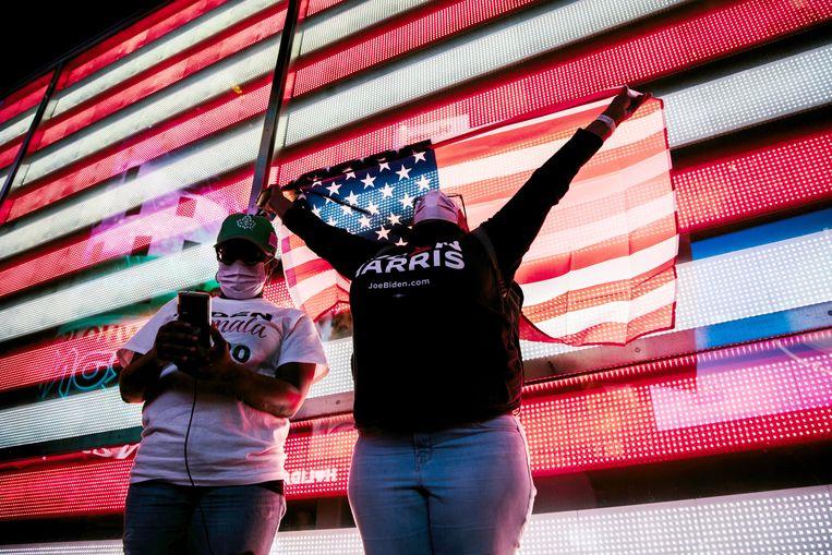 Biden- en Harris-fans voor de schermen op Times Square.  Beeld EPA