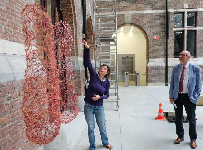 Gedeputeerde Luk Lemmens luistert aandacht naar kunstenares Inge De Zutter bij haar werk 'Samen Drie'.