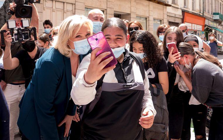 Een fan in Saint-Chamond maakt een selfie met Marine Le Pen. 'Zij is de openlijk xenofobe rechterzijde nu liever kwijt dan rijk.'  Beeld Photo News