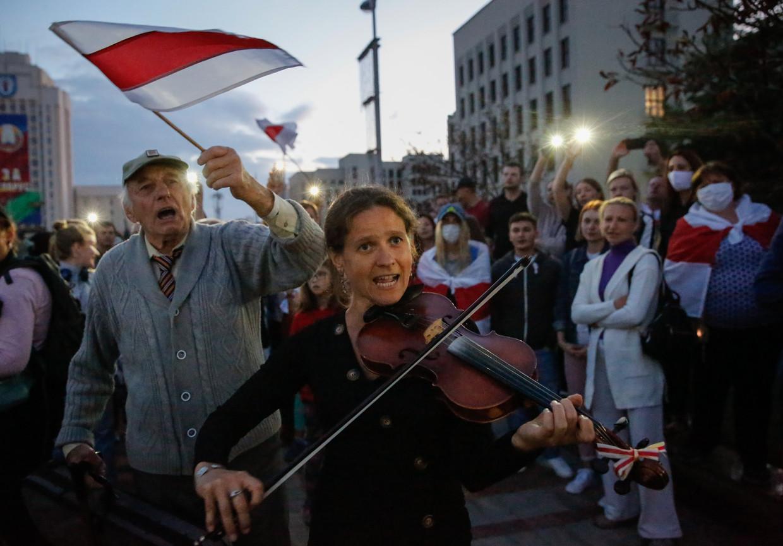 Een vrouw speelt viool op een demonstratie tegen Loekasjenko in Minsk. Beeld EPA