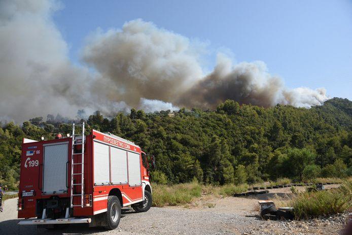 Un camion de pompiers intervient lors d'un incendie de forêt près du village de Ziria, à l'ouest de Patras, en Grèce, samedi 31 juillet 2021.  L'incendie, qui s'est déclaré en haut d'un versant de montagne, s'est dangereusement rapproché des villes côtières et les pompiers ont envoyé un bateau pour aider à une éventuelle évacuation des personnes.