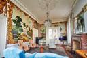 De salonkamer met muurschilderingen die mensen uit België en Frankrijk maakten in ruil voor kost en inwoning