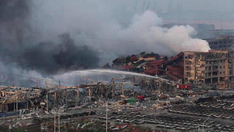 Reddingswerkers tussen honderden uitgebrande wagens en vernielde gebouwen in Tianjin.