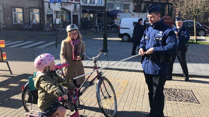 Een politieagent toont voorbijgangers in Diest wat de minimumafstand is bij 'social distancing'.