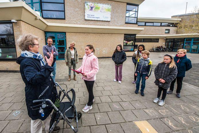 Marrie ter Horst overhandigt de brieven van de bewoners aan de kinderen van basisschool de Triangel.