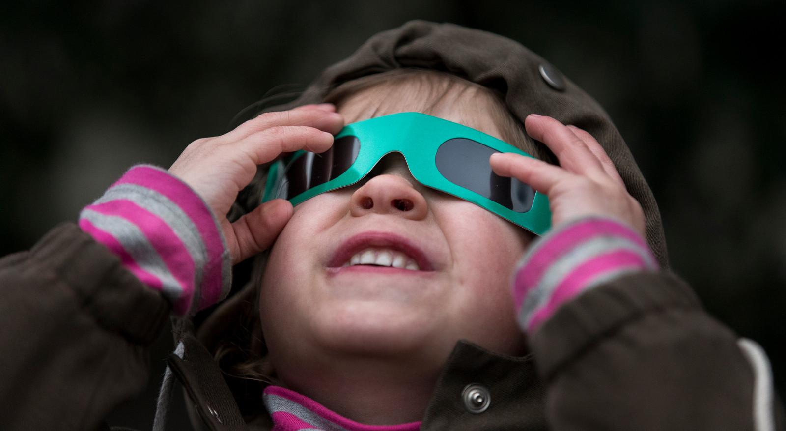 Beeld ter illustratie: Een kind bekijkt de zonsverduistering mét eclipsbril in 2015.