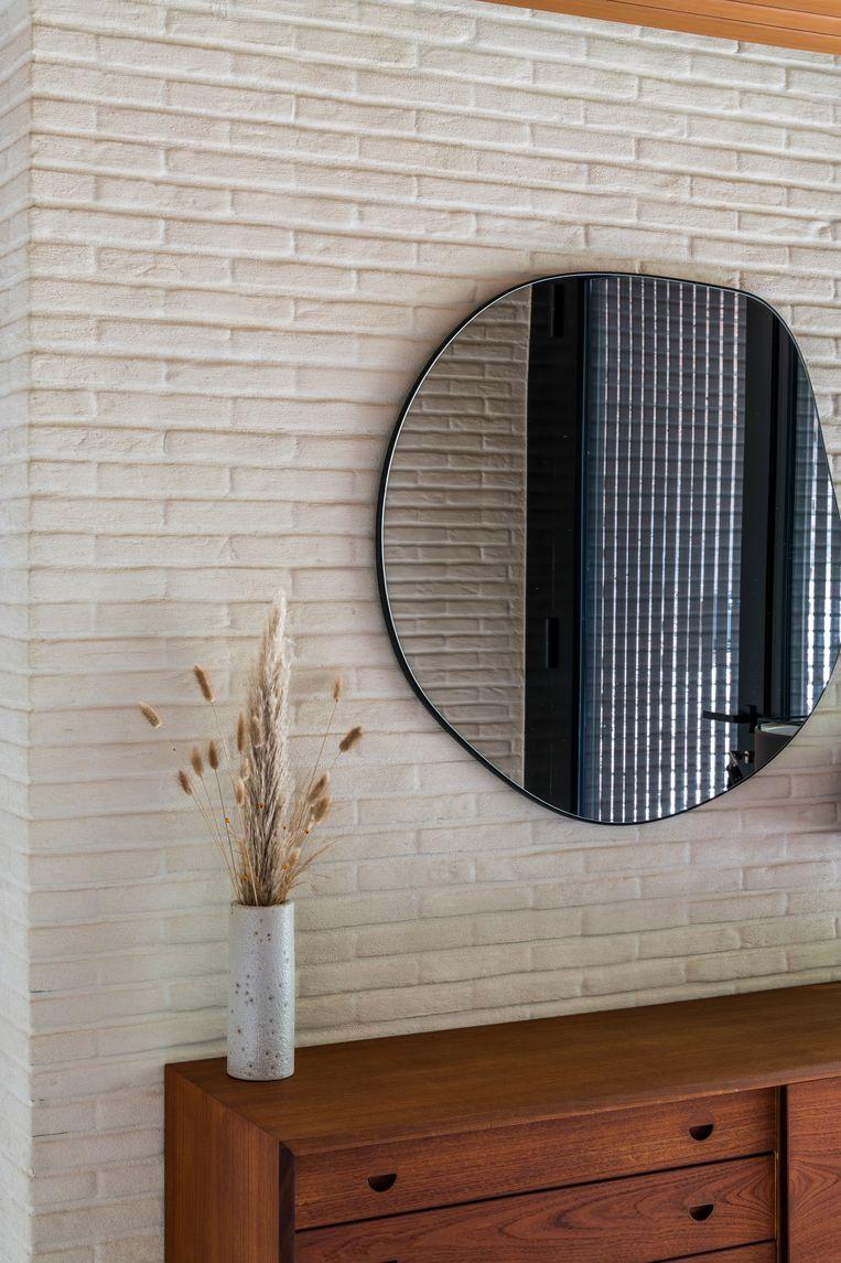 Ronde accenten, zoals de spiegel in de inkomhal of de ovalen tafel in de eetkamer, verzachten de hoekige ruimtes.  Beeld Luc Roymans