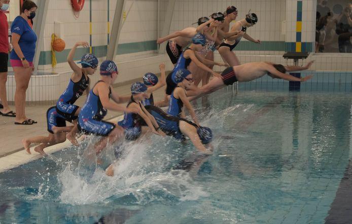 Leden van het Kempisch Triatlon Team springen in het zwemwater