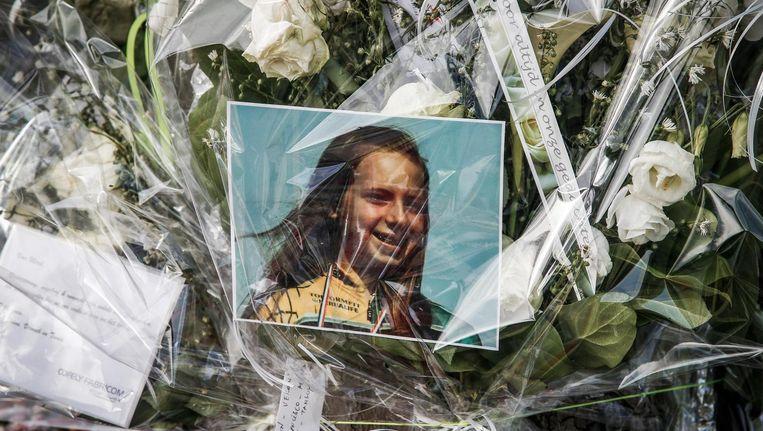 Een foto van Merel De Prins op een bos bloemen die ter nagedachtenis aan haar op de plek van het ongeluk is gelegd. Beeld belga