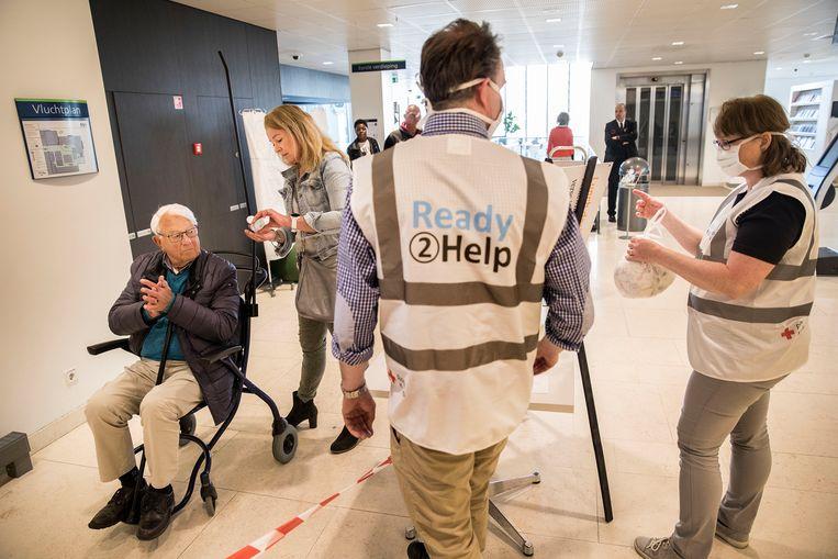 vrijwilligers van het Rode Kruis meten de temperatuur op in een ziekenhuis. Beeld Arie Kievit