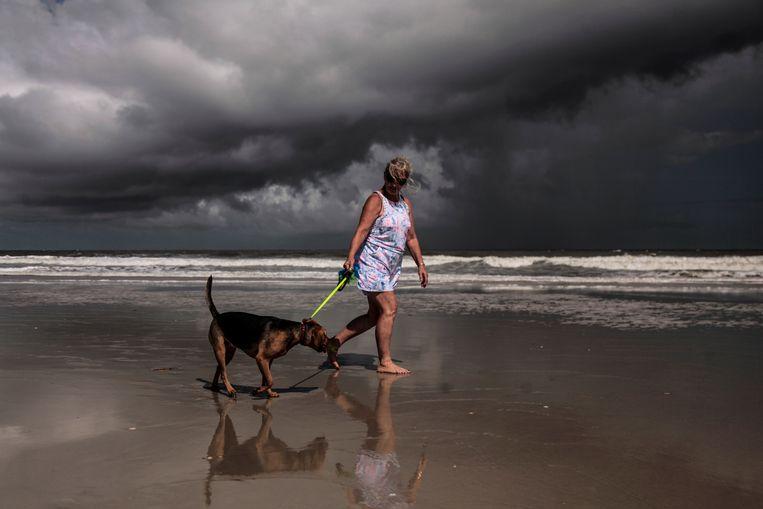 Een vrouw laat nog even haar hond uit voor het noodweer losbarst. Beeld REUTERS