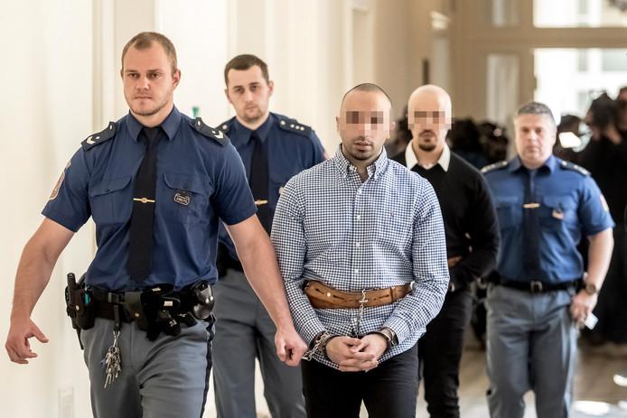 Arash (geruite blouse, voorgrond) en Armin op weg naar de rechtszaal.
