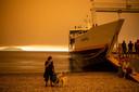 Een vrouw staat met haar hond bij de ferry. Op Evia woeden bosbranden.