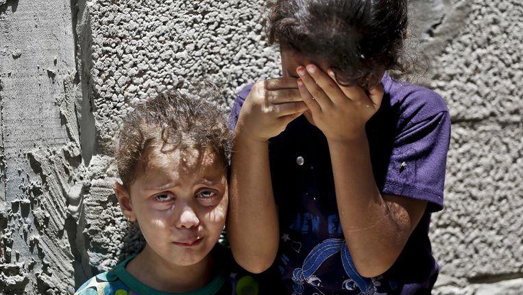 Twee Palestijnse meisjes huilen als het lichaam van een gezinslid voor de begrafenis uit huis wordt gehaald. De man is omgekomen bij een raketaanval. Beeld ap
