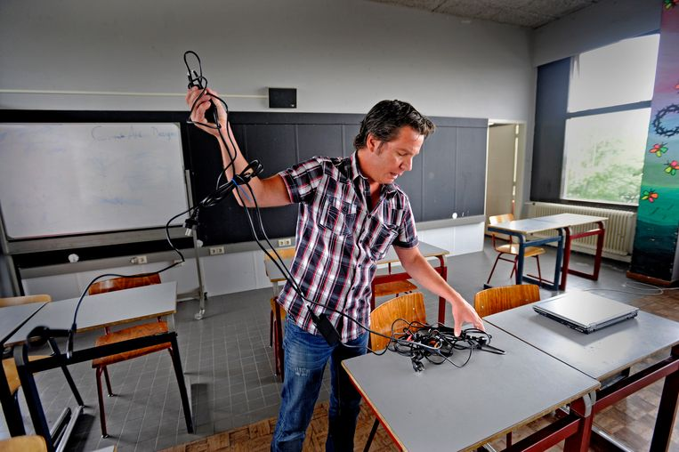 Onderwijsassistent Leo Bonomo zet de laptops neer voor het eindexamen Spaans op het Alberdingk Thijm mavo in Hilversum.  Beeld Raymond Rutting / de volkskrant