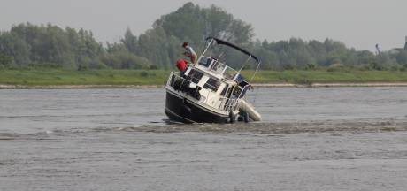 Bootje met passagiers vaart op een krib van de Waal