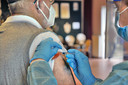 Een man wordt ingeent tegen het griepvirus.