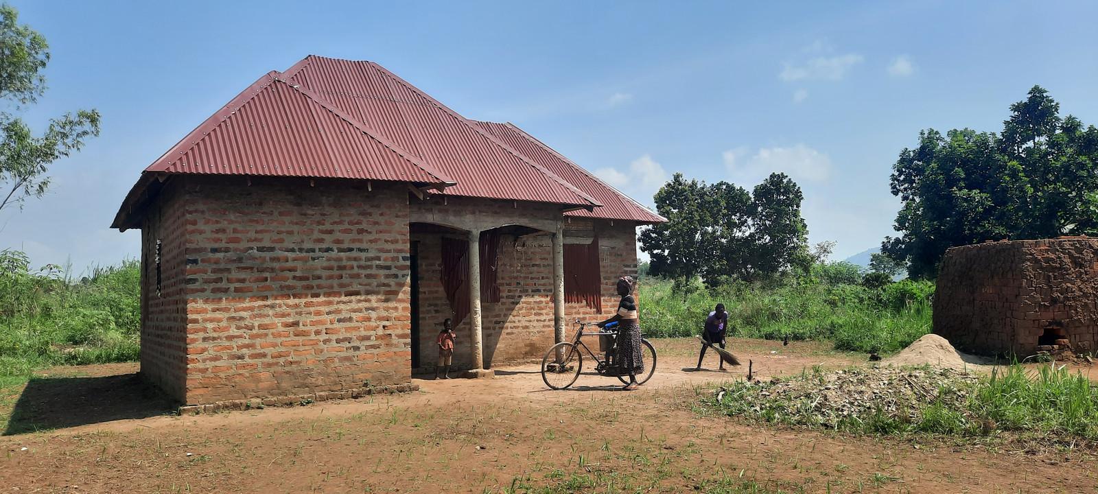 Een jaar geleden was Kyataruga een dorp in de brousse bestaande uit schamele hutjes met strooien daken. Nu zie je overal bakstenen huizen met metalen, regenbestendige daken. Zoals deze nieuwe woonst van Vote Kabanyoro en haar man Gerald.