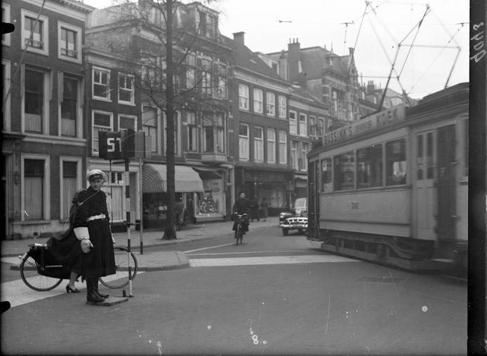 De verkeersagent met zijn bord op een paal die hij tijdens 'spitsuur' in een metalen gat in de Herengracht stak. Pas als er stop stond mochten voetgangers oversteken.