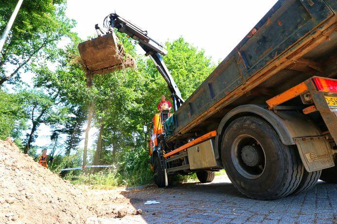 De grond wordt afgegraven waar de vermoedelijke drugsvaten gevonden werden.