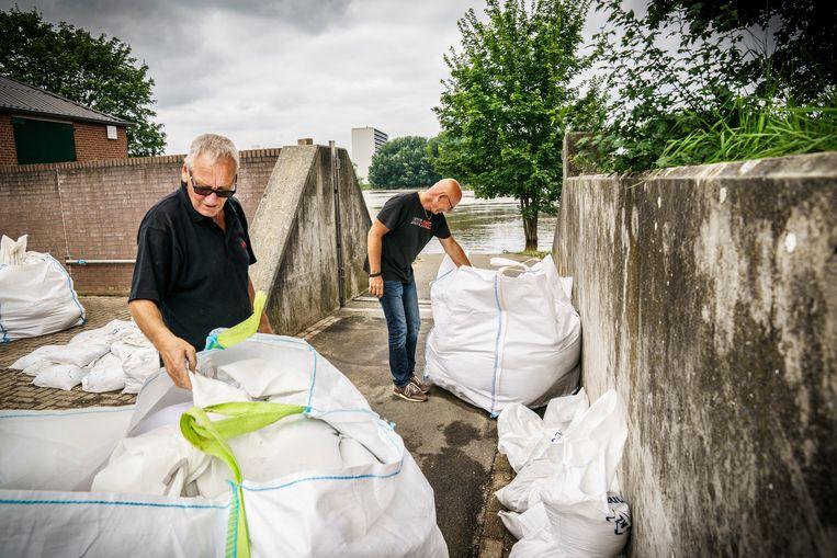 Jan Wilmer (zonnebril) en Luuc Driessen van Kanovereniging Viking Venlo zijn bezig om de waterschotten en zandzakken op te ruimen nadat het water van de Maas weer is gezakt.  Beeld Maikel Samuels