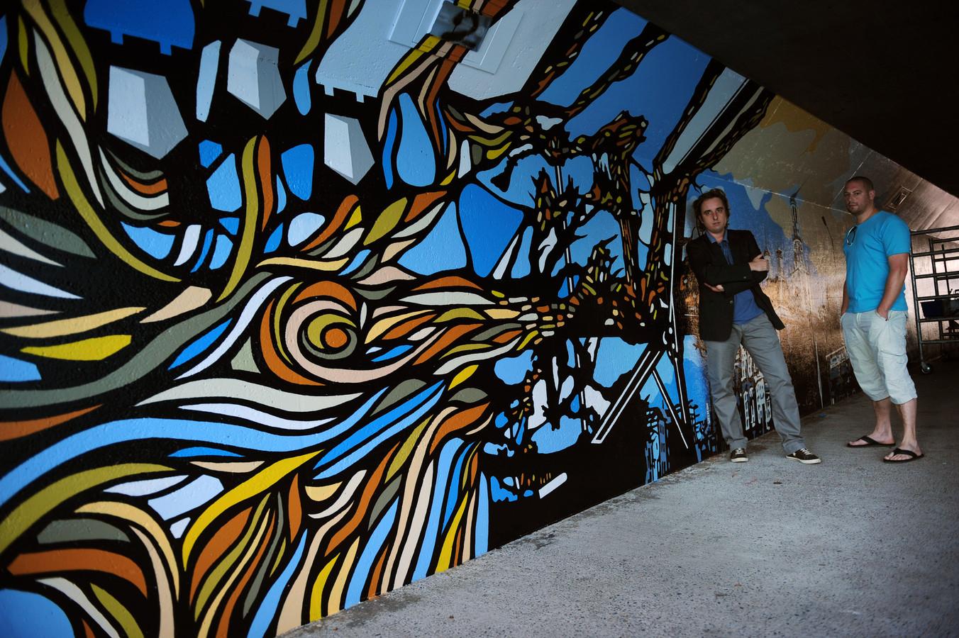 Kunstenaars Stijn de Wilde (l) en Mario Pasetto bij een deel van de muurschildering.