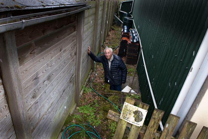 Ingen Arie van der Klift staat in de kelderingang waar onderduikers uit vluchte naar het andere huis als de Duitsers voor de deur stonden.