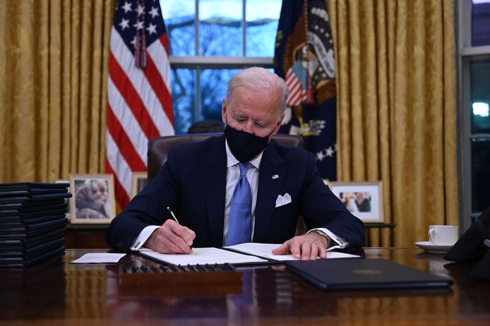 De kersverse Amerikaanse president Biden tekent een aantal presidentiële decreten in het Oval Office.