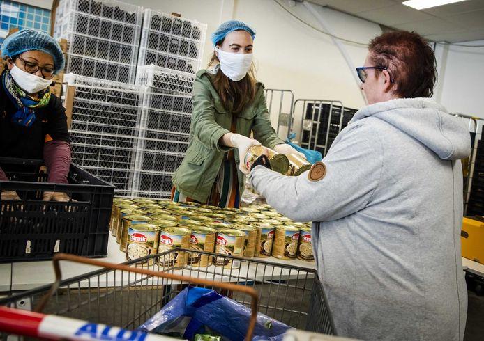 Vrijwilligers van de Voedselbank in Tilburg delen eten uit aan minima.
