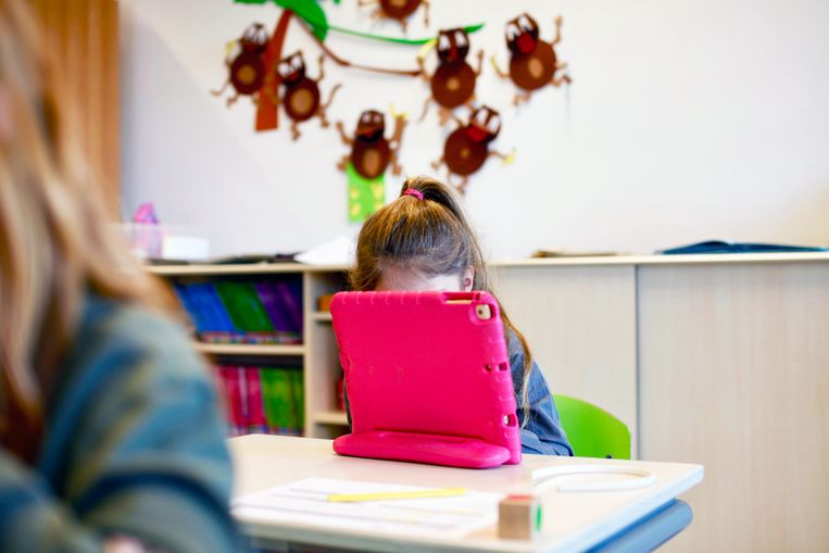Een klein meisje zit achter een tablet.  Beeld Hollandse Hoogte / Richard Brocken