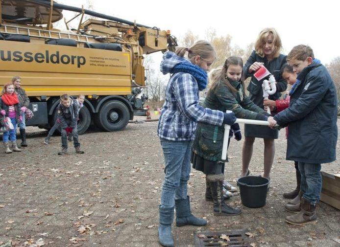 Wethouder Esther Verhagen bouwt, samen met de kinderen, een rioolbuis. foto Ruben Schipper