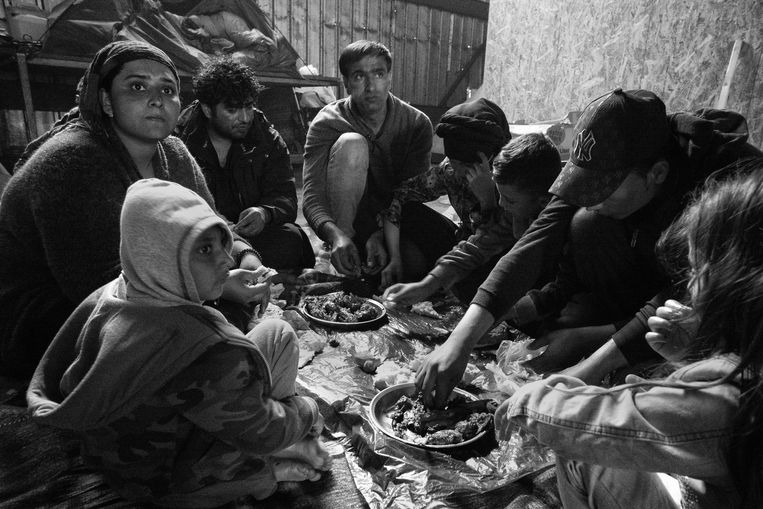 Sommige Afghaanse gezinnen nuttigen hun suikerfeestmaaltijd samen in de oude vliegtuighangar. Beeld Eddy van wessel